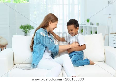 Happy mother with adopted African-American boy sitting on couch at home