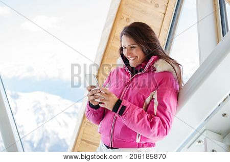 Young woman in warm jacket using mobile phone. Cheerful woman in pink jacket reading message while traveling in mountain during winter. Happy smiling woman typing on smartphone in ski resort.