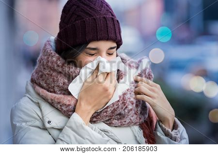 Pretty young woman blowing her nose with a tissue outdoor in winter. Young woman getting sick with flu in a winter day. Woman with a cold.