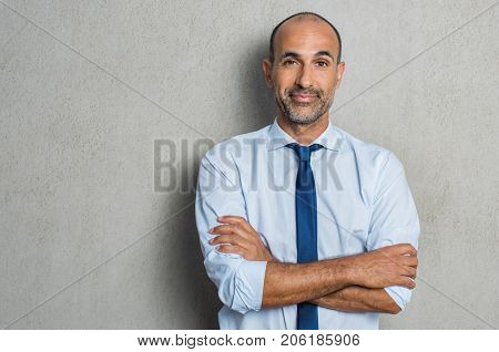 Portrait of happy mature businessman standing against grey background while looking at camera. Proud senior business man against grey wall with copy space. Executive manager with arms crossed smiling.