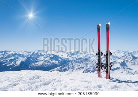 Pair of skis in snow with copy space. Red skis standing in snow with winter mountains in background. Winter holiday vacation and skiing concept.