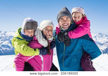 Happy family with two children on winter vacation in mountain. Father and mother giving piggyback ride daughter and smiling son. Portrait family looking at camera with snowy mountains in background.