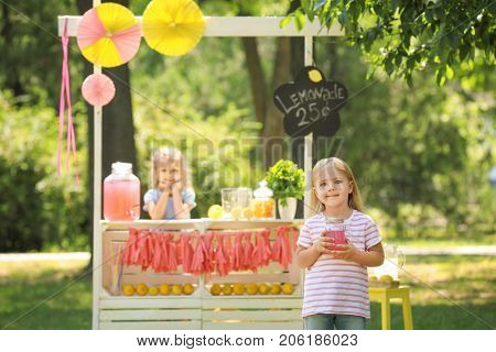 Adorable little girl with jar near lemonade stand in park