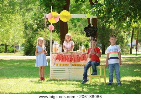 Happy children near lemonade stand in park