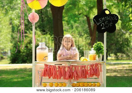 Cute little girl waiting for customers at lemonade stand in park