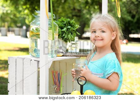 Little girl with jar near lemonade stand in park