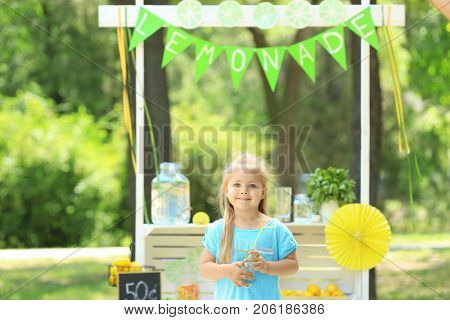 Cute smiling girl with glass near lemonade stand in park