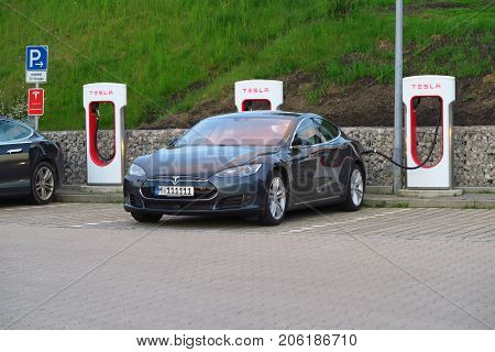 INNSBRUCK AUSTRIA - MAY 18 : An electric car recharges at a Tesla Supercharger free charging station on May 18 2016.