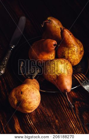 Few Golden Pears with Fork and Knife on Wooden Table. Vertical Orientation.