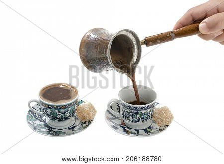 Pouring Turkish coffee in cup over white background.