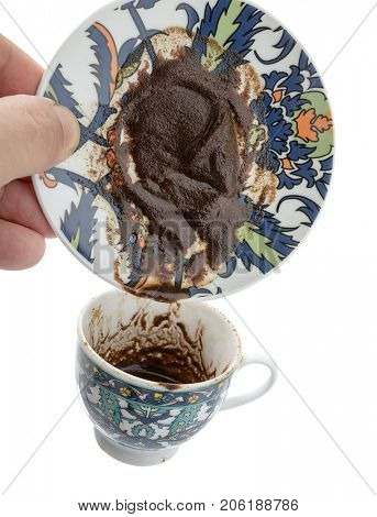 Male hand turns Turkish coffee cup upside down for coffee fortune telling.
