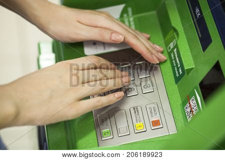 Female arms, Green ATM - entering pin