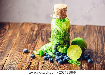 Bottle of Detox Water Infused with Lime, Mint and Blueberry and Ingredients on Table. Copy Space on the Left.