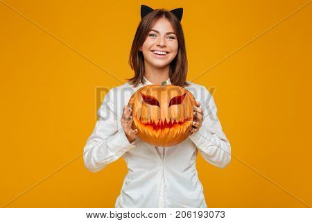 Image of cheerful young woman dressed in crazy cat halloween costume over yellow background with pumpkin.