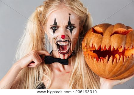 Dangerous crazy blonde woman in halloween clown make-up and blood streaks holding curved pumpkin and looking at camera isolated over gray background