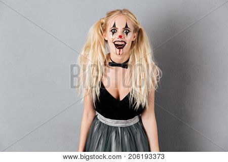 Portrait of a crazy laughing blond woman in halloween clown make-up and blood streaks looking at camera isolated over gray background