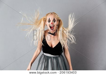 Portrait of a mad laughing blond woman in halloween clown make-up and blood streaks looking at camera isolated over gray background