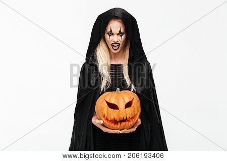 Portrait of a scary angry blonde woman in halloween make-up and black robe holding curved pumpkin isolated over white background