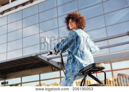 View from below of pleased curly woman sitting on modern motorbike outdoors and looking away