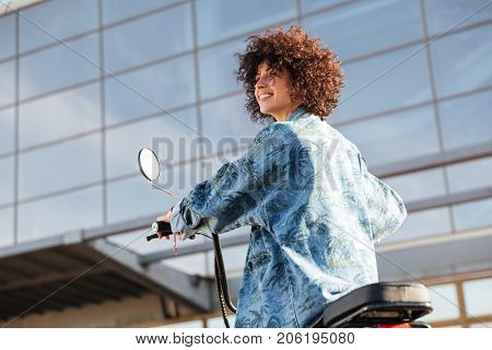 View from below of smiling curly woman sitting on modern motorbike outdoors and looking away
