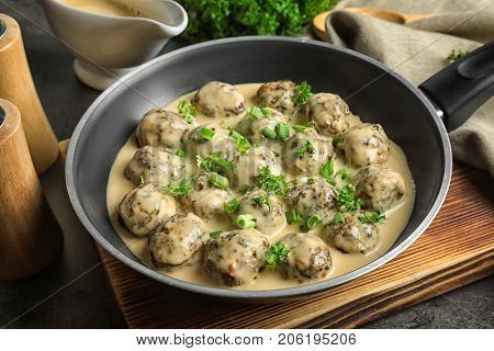 Frying pan with delicious meatballs in sauce on table