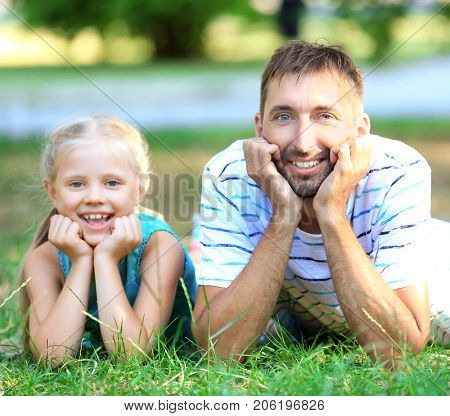 Young man with little girl lying on grass in park