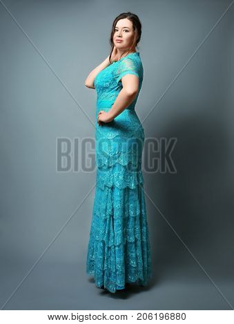 Beautiful overweight woman in lacy dress on grey background