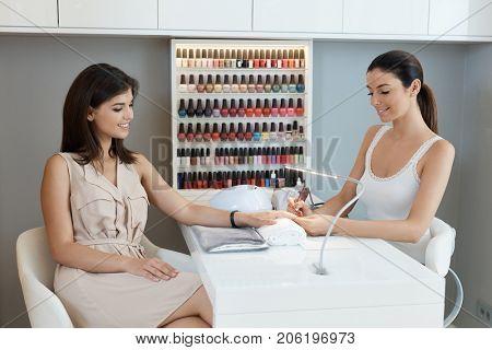 Beautiful woman getting nail treatment at manicurist.