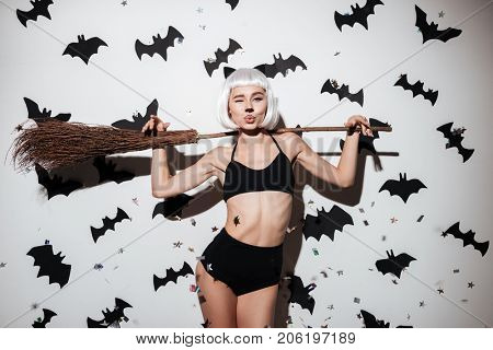 Portrait of a sexy young woman in halloween cat costume posing and winking with a broom over bats and confetti background