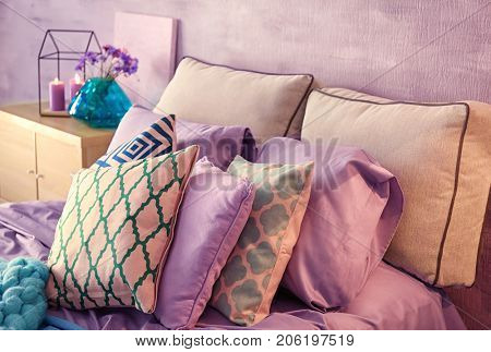 Lilac accent in modern interior. Pillows on comfortable bed at home