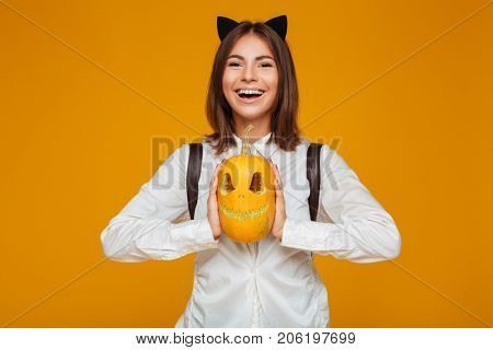 Portrait of a smiling teenage schoolgirl in uniform with backpack holding halloween pumpkin and looking at camera isolated over orange background