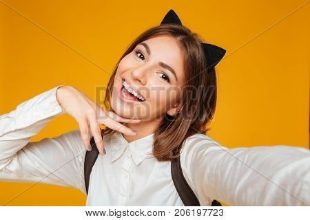 Close up portrait of a pretty teenage schoolgirl in uniform with backpack taking a selfie while standing and posing isolated over orange background