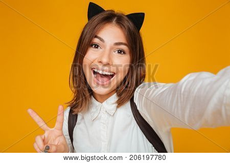 Close up portrait of a cheerful teenage schoolgirl in uniform with backpack taking a selfie while standing and showing victory gesture isolated over orange background