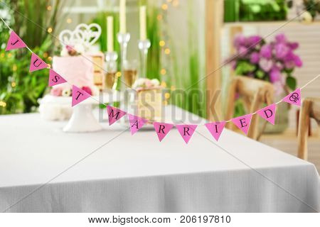 Garland with text JUST MARRIED, indoors. Concept of lesbian wedding