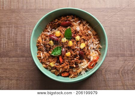 Chili con carne in bowl on wooden background