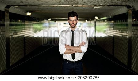 Determined young businessman standing arms crossed in underpass, looking at camera.