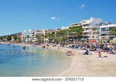 MAJORCA, SPAIN - SEPTEMBER 5, 2017: People on the beach at Puerto Pollensa on the Spanish island of Majorca. The popular holiday destination is the most Northerly town on the island.