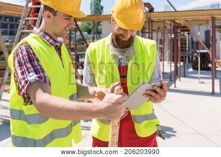 Two young construction workers smiling while using a tablet for online communication through social media during break at work