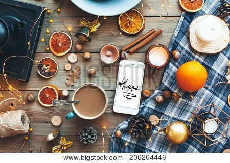 Flat lay of seasonal home craft decor. Coffee or tea break for home relax. Winter or autumn concept, warm homely scene. Smart phone with Hygge text on screen.