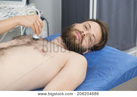 Patient Undergoing Ultrasound Test On Chest From Doctor