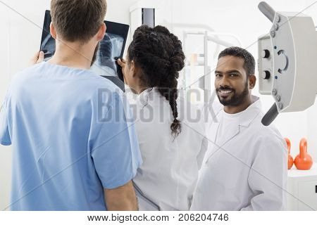 Radiologist With Colleagues Analyzing X-ray In Hospital
