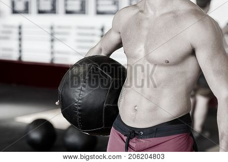Midsection Of Shirtless Trainer With Medicine Ball