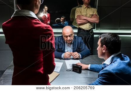 Middle-aged man thinking about his statement and the criminal charge while sitting down during interrogation in the office of the police station