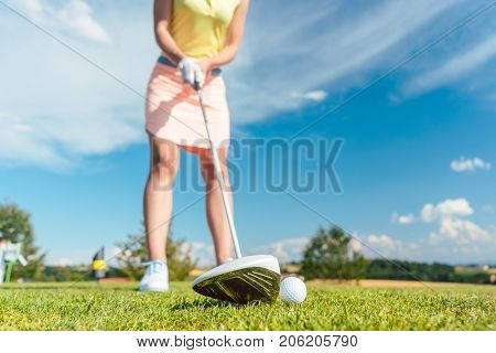 Close-up of a golf ball next to a professional club held by a female player ready to strike, during game on the putting green outdoors in a sunny day
