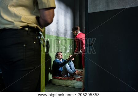 Dedicated female attorney visiting a young male inmate while helping him with the legal procedures in an obsolete prison cell during custody