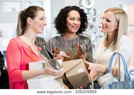 Women friends on a shopping trip discussing sandals and buying shoes