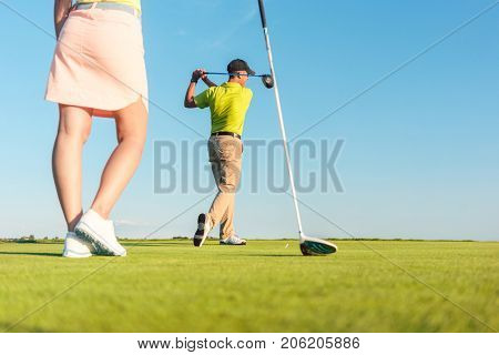 Low-angle full length view of man playing professional golf with his female partner during matchplay, for two players outdoors in a sunny day of summer