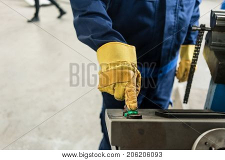 Close-up of the hand of a worker wearing protective gloves while pressing the button of an industrial machine