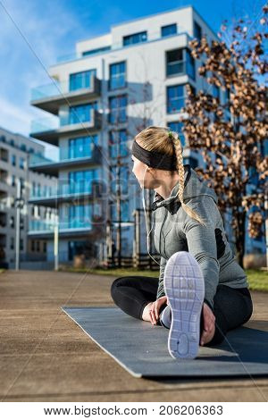 Fit young woman with a healthy lifestyle daydreaming while stretching her leg on a mat during outdoor warm-up exercises in a sunny day