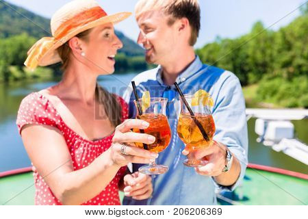 Happy couple in love on river cruise drinking coctails in summer enjoying their time